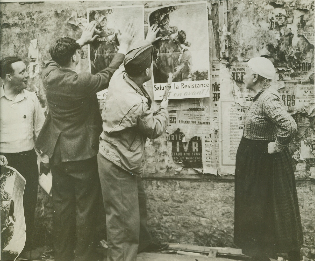 Down With the Old Up With the Free, 8/22/1944. FRANCE -- Residents of Columbierre help an American soldier cover the remnants of Nazi display propaganda with Allied posters. An elderly French woman surveys the work with satisfaction. Credit (OWI Photo from ACME);