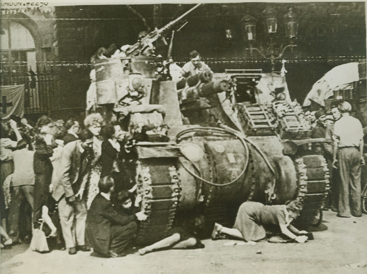 Seek Protection from Tank, 8/28/1944. PARIS -- Panic-stricken Parisians crouch close to a French armored tank for cover as snipers bullets whistle down from Notre Dame Cathedral. The terrified crowd was watching General De Gaulle enter the noted Cathedral for Thanksgiving services when the snipers attacked. British War Office Photo. Credit: (Army Radiotelephoto from ACME);