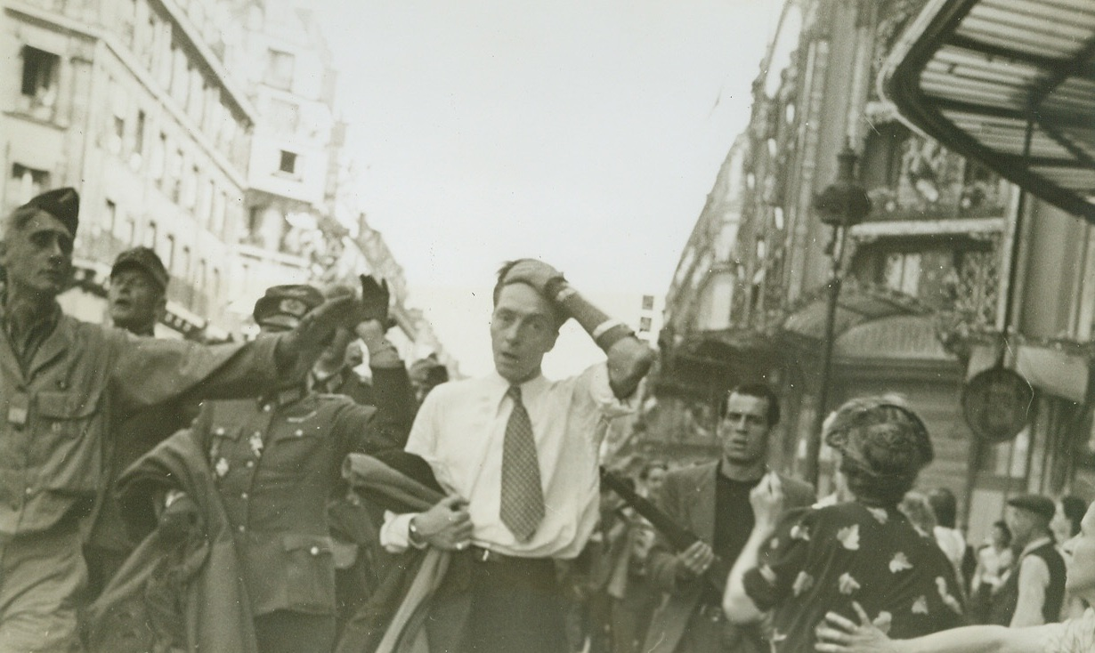 The Last Time They'll See Paris, 8/28/1944. FRANCE -- Captured Nazis are marched through Paris street under the careful and alert guard of the E.F.I. The man clasping his head is a German soldier who had dressed in civilian clothes and sniped at the French during the last days of the battle for the French capital. Credit (ACME Photo by Bert Brandt for the War Picture Pool);