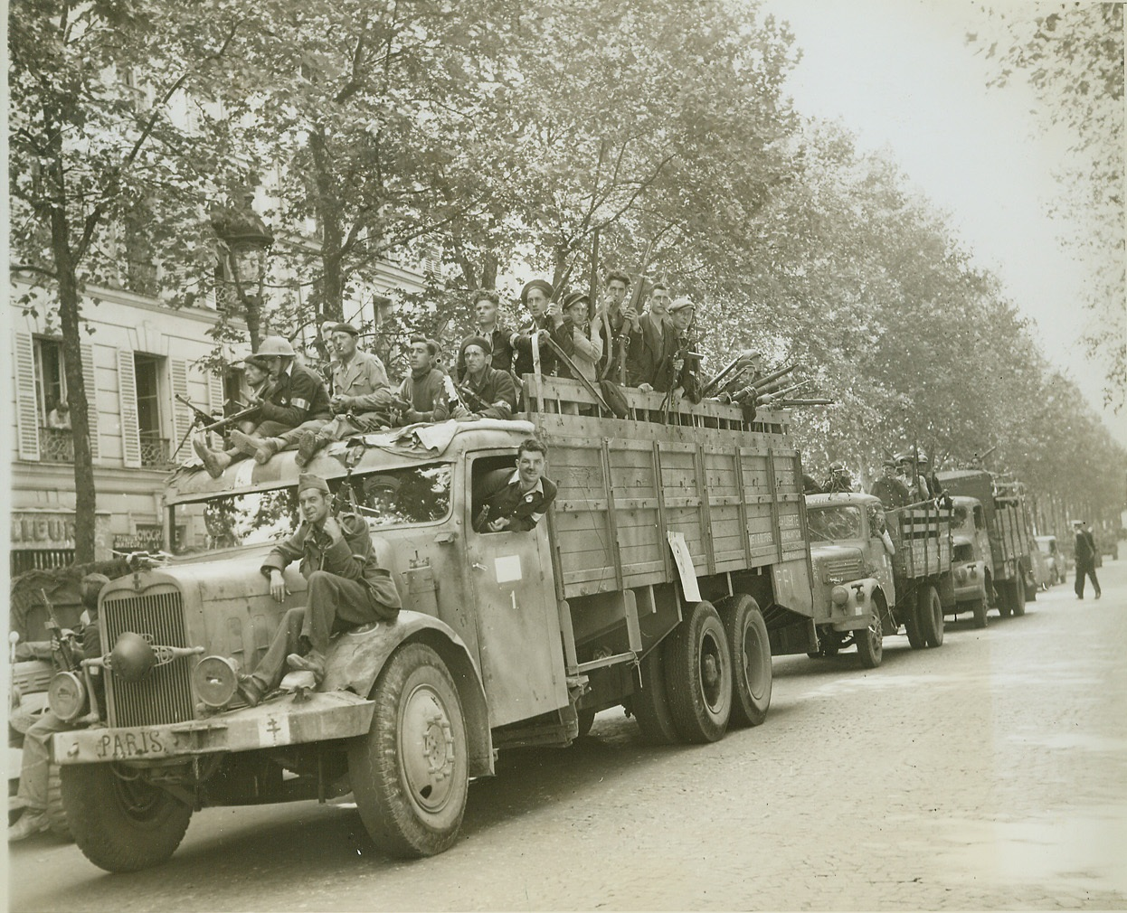 Sniper Hunt, 8/28/1944. PARIS -- Scanning streets and rooftops, FFI warriors ride through Paris in captured German vehicles, hunting German snipers and French Fascists fighting last-ditch resistance in the French capital. Note the Cross of Lorraine painted on the bumper of the captured truck in foreground. Credit: - WP- (ACME Photo by Andy Lopez for the War Picture Pool);
