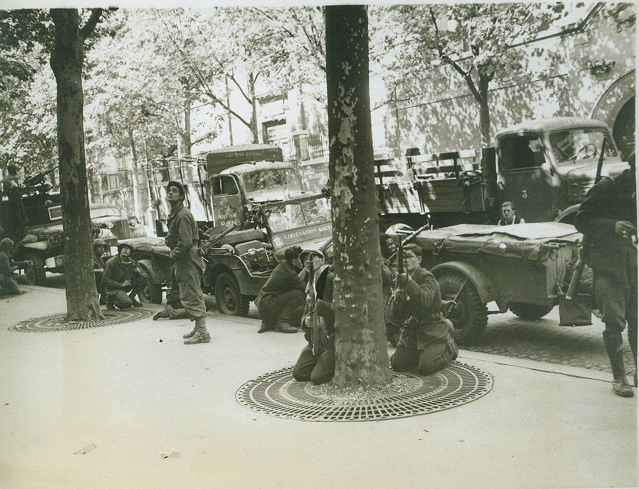 Snipers Above, 8/28/1944. PARIS -- Eyes on a rooftop where an enemy sniper has been spotted, men of the FFI and the Second French Armored Division are ready to let 'em have it during street fighting in the heart of Paris. Behind the valiant patriots are German trucks that were captured by the Maquis. Credit:-WP-(ACME Photo by Andy Lopez for the War Picture Pool);