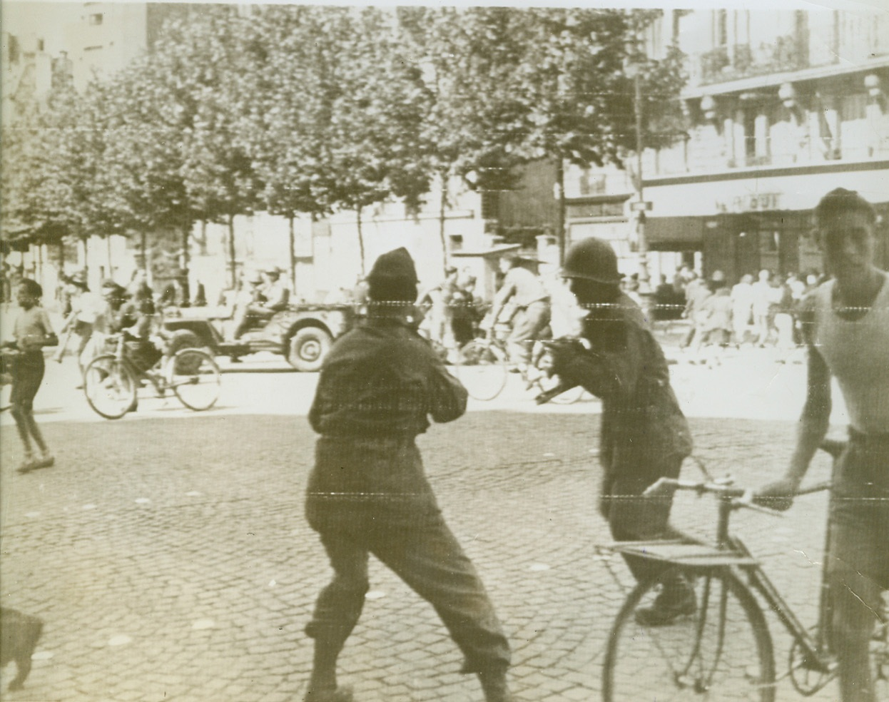 Paris Celebration Ends in Riot, 8/27/1944. Paris, France—A few minutes before the scene of a triumphal procession celebrating the liberation of Paris, this street in the vicinity of the Eiffel Tower is now filled with people scrambling to escape the rifle fire of Nazis and collaborationists quartered in nearby buildings. It was during this procession that an attempt was made on the life of Gen. de Gaulle. The photographers in the foreground, taking pictures as the people scramble for shelter, are probably war picture pool correspondents.  Credit: ACME photo via Signal Corps;