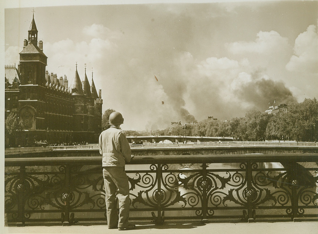 Across the Bridge Paris Burns, 8/30/1944. France—An Allied soldier stands on one of the many bridges across the Seine in Paris to watch fires burning on the outskirts of the French capital during the spasmodic fighting that took place before the city was completely liberated.  Credit: ACME photo by Bert Brandt, War Pool correspondent;