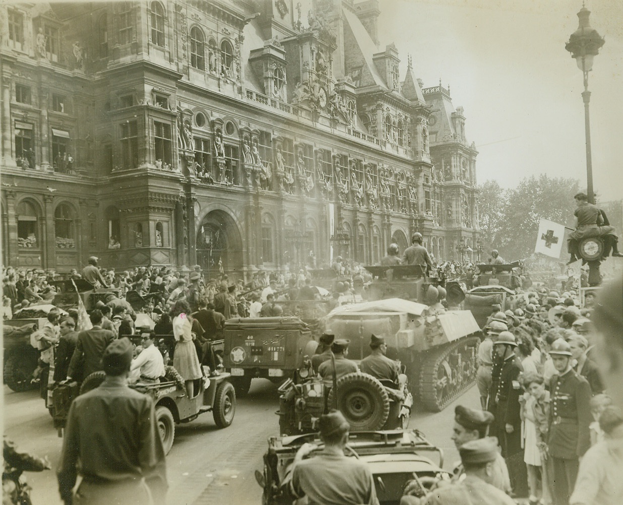 Stage Set For Panic, 8/28/1944. Paris—This was the scene in the Place de L'Hotel de Ville before snipers sent a panic-stricken crowd scurrying for their lives during the official reception for General Charles de Gaulle. The street is jammed with Allied armored vehicles and hundreds of celebrating Parisians. At left, spectators jam the windows of the Hotel de Ville, while at right one spectator has climbed to a perch halfway up a lamp post to witness the celebration.  Credit: ACME photo by Andy Lopez for the War Picture Pool;