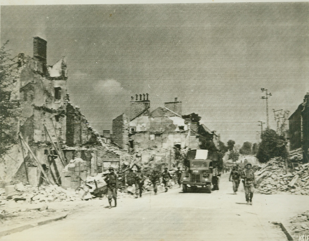 In Pursuit of Germans, 8/8/1944. France—American Infantrymen move through Mayenne on the heels of German forces, fleeing in the face of the American blitz offensive. Buildings were blasted by U.S. bombers. Credit: Army radiotelephoto from ACME;