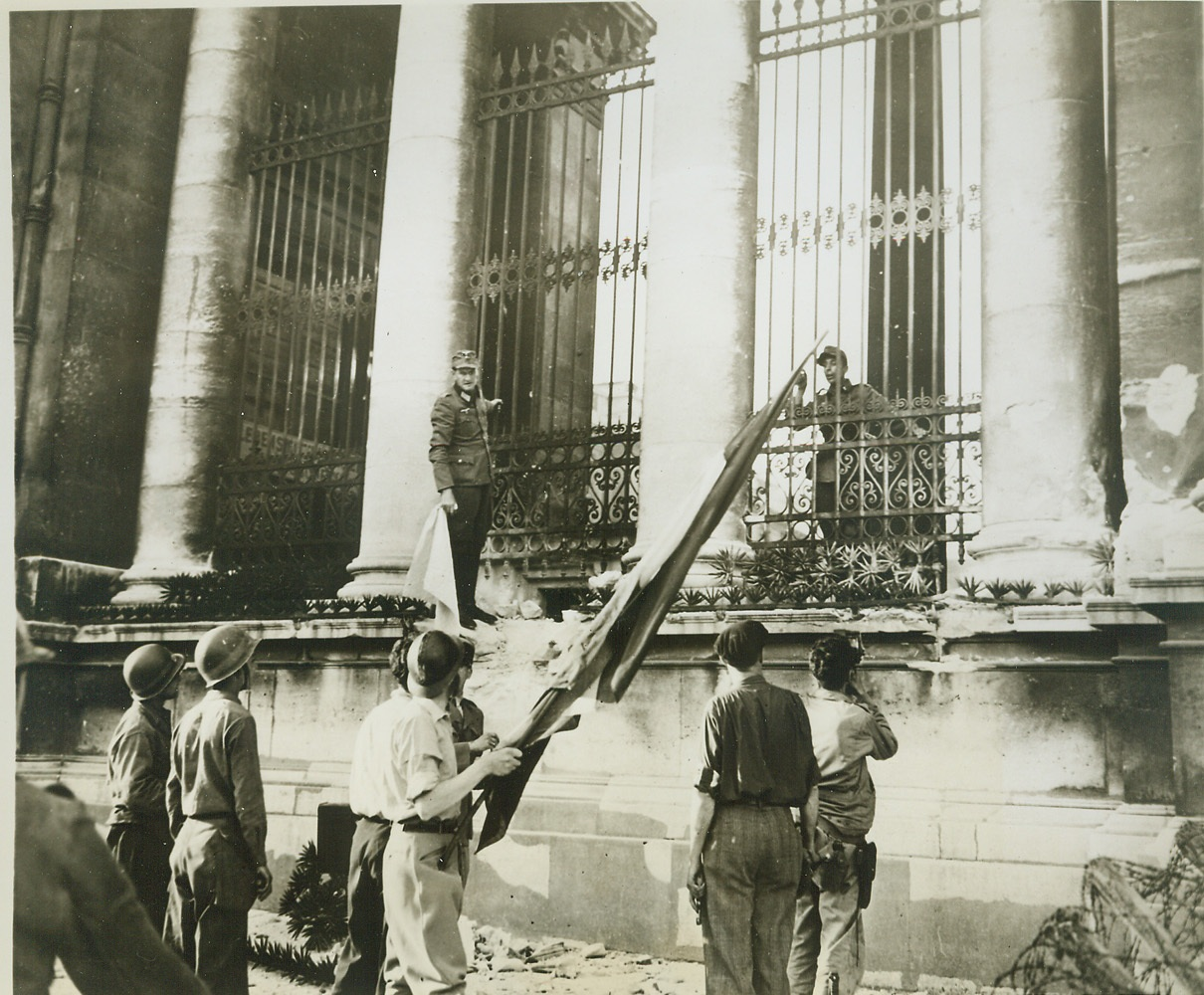 France Regains Its Chamber of Deputies, 8/30/1944. France—With a Nazi garrison barricaded behind him, a German officer hangs onto rail of the Chamber of Deputies in Paris while negotiating for surrender to the French partisans. He holds the white flag of truce while a French soldier in the foreground has the Tricolor ready to hoist as a signal of victory when surrender is complete.  Credit: ACME;