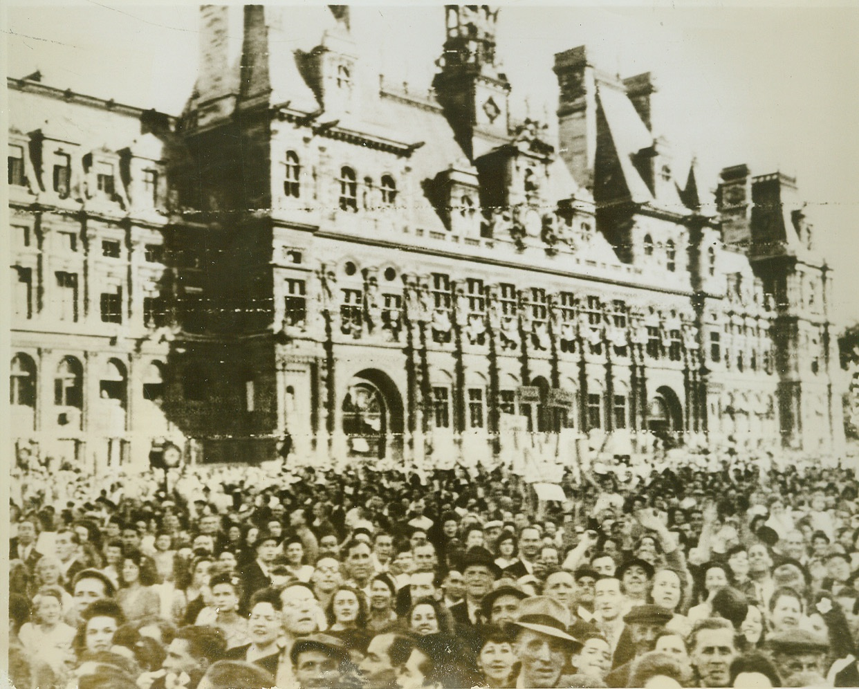 Celebrants Mass in Paris Streets, 8/28/1944. Paris—With faces reflecting the joy of being free once more, Parisians mass in front of the Hotel de Ville in Paris to celebrate the liberation of their city. Shortly afterward, as their voices raised in triumphant cheers for Gen. de Gaulle, shots rang out over their exuberant voices as snipers preyed on the assembly. The General, leading a triumphal procession, narrowly escaped death or injury.  Credit: Signal Corps radiotelephoto from ACME;