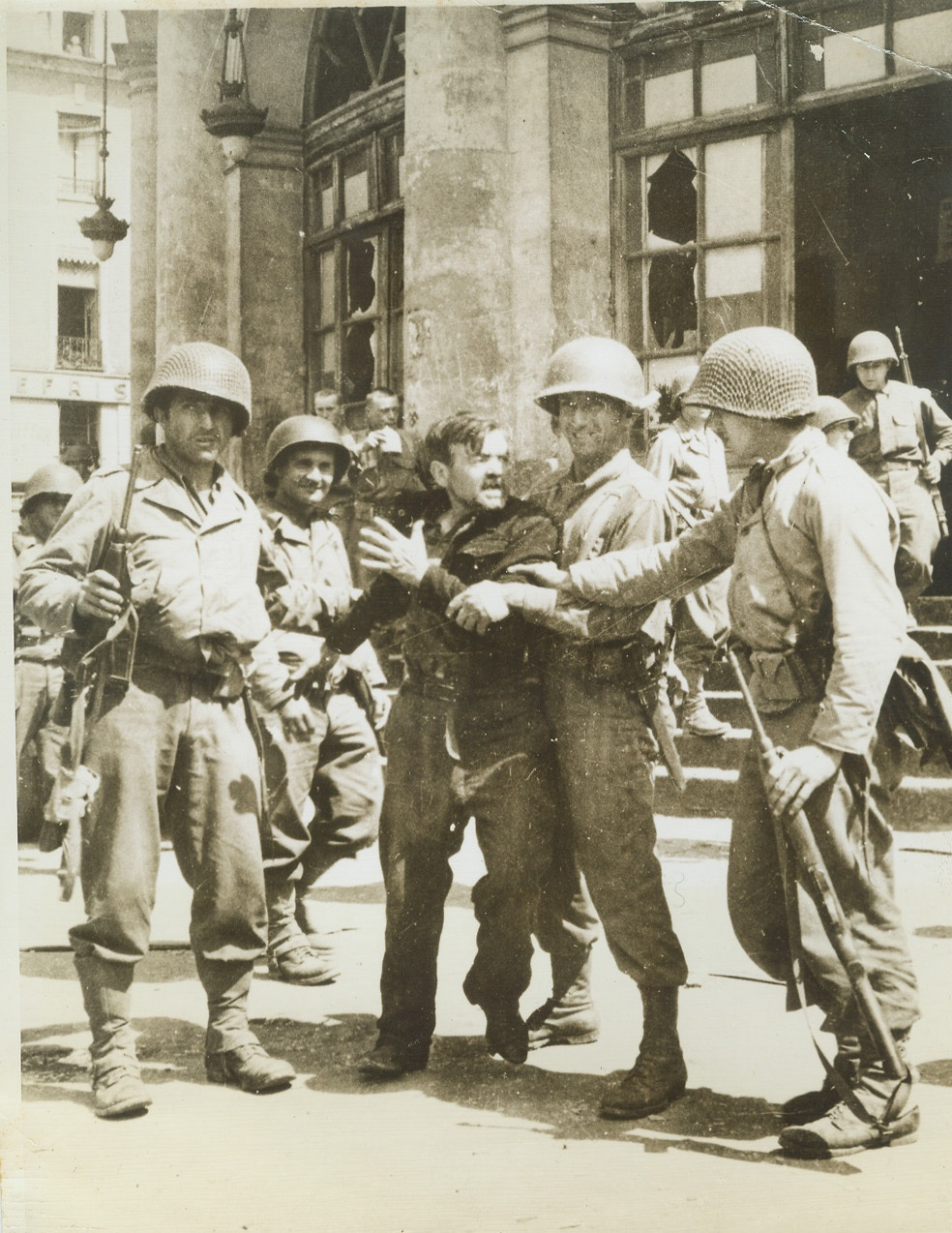 Underdog Turns on Nazis, 8/11/1944. Rennes, France—While American soldiers restrain him, this French patriot struggles to free himself and vent his wrath on disarmed Nazi prisoners of war gathered on the Rennes City Hall steps. Finally freed of Nazi oppression, he fought to get at those who were responsible for the tyrannical treatment.  Credit: ACME;