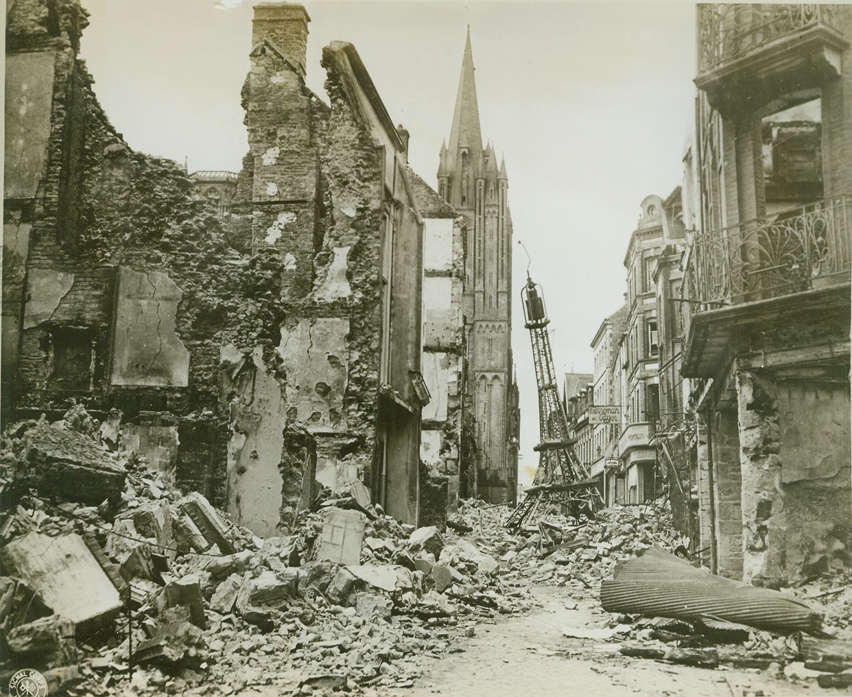Miniature Eiffel Tower Amid Wreckage, 8/3/1944. France—Flanked by war-torn buildings, a small replica of the famous Eiffel Tower rests atop a heap of rubble in a Coutances Street. In the center, background, is the Cathedral, seemingly undamanged. Credit: U.S. Army photo from ACME;