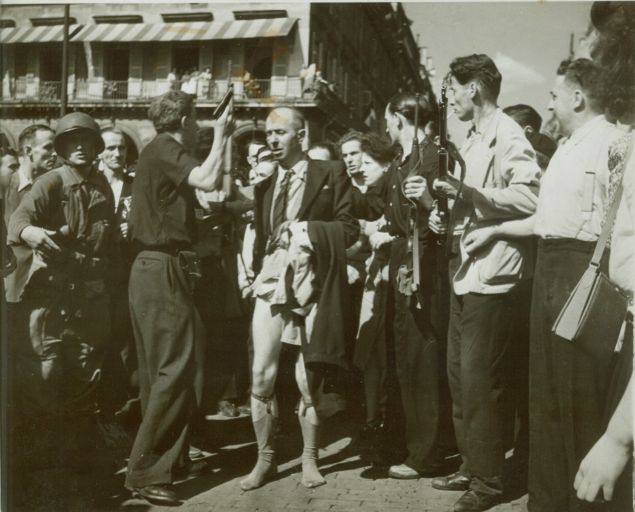 """Collaborationist Who Needed """"Protective Custody"""", 8/28/1944. Paris—This collaborationist who lost his pants to an angry group of Parisians is shown being saved by the F.F.I. and taken into their protective custody. Credit: ACME photo by Bert Brandt for the war picture pool;"""