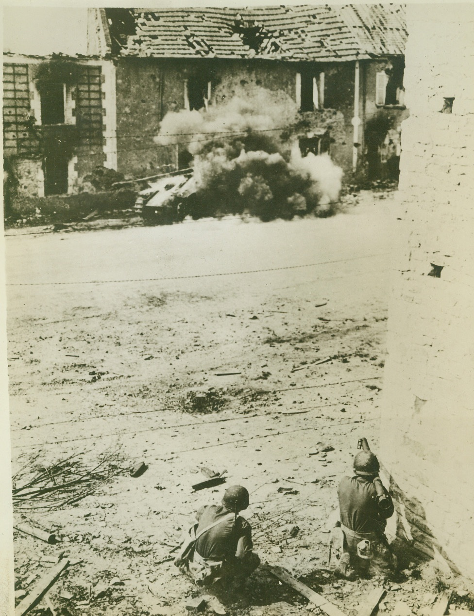 Removing German Tank Obstacle, 8/1/1944. Normandy, France—The camera records the instant when the bazooka guns fired by the Allied soldiers in the foreground score direct hits on the German tank in the rear, and the vehicle goes up in a cloud of flame and smoke. The soldiers were aiming at the wrecked building which housed German snipers, but the tank was blocking their attack. Credit: ACME;