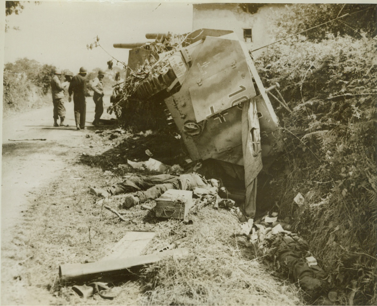 Where Nazi Panzers Were Trapped, 8/3/1944. France—Wrecked German armored vehicles and their dead crew members lie along this road in Roncey, where they were trapped by American troops and destroyed by supporting Allied fighters and rocket bombers. The U.S. Second Armored Division sprung the trap on the Nazis. Credit: ACME;
