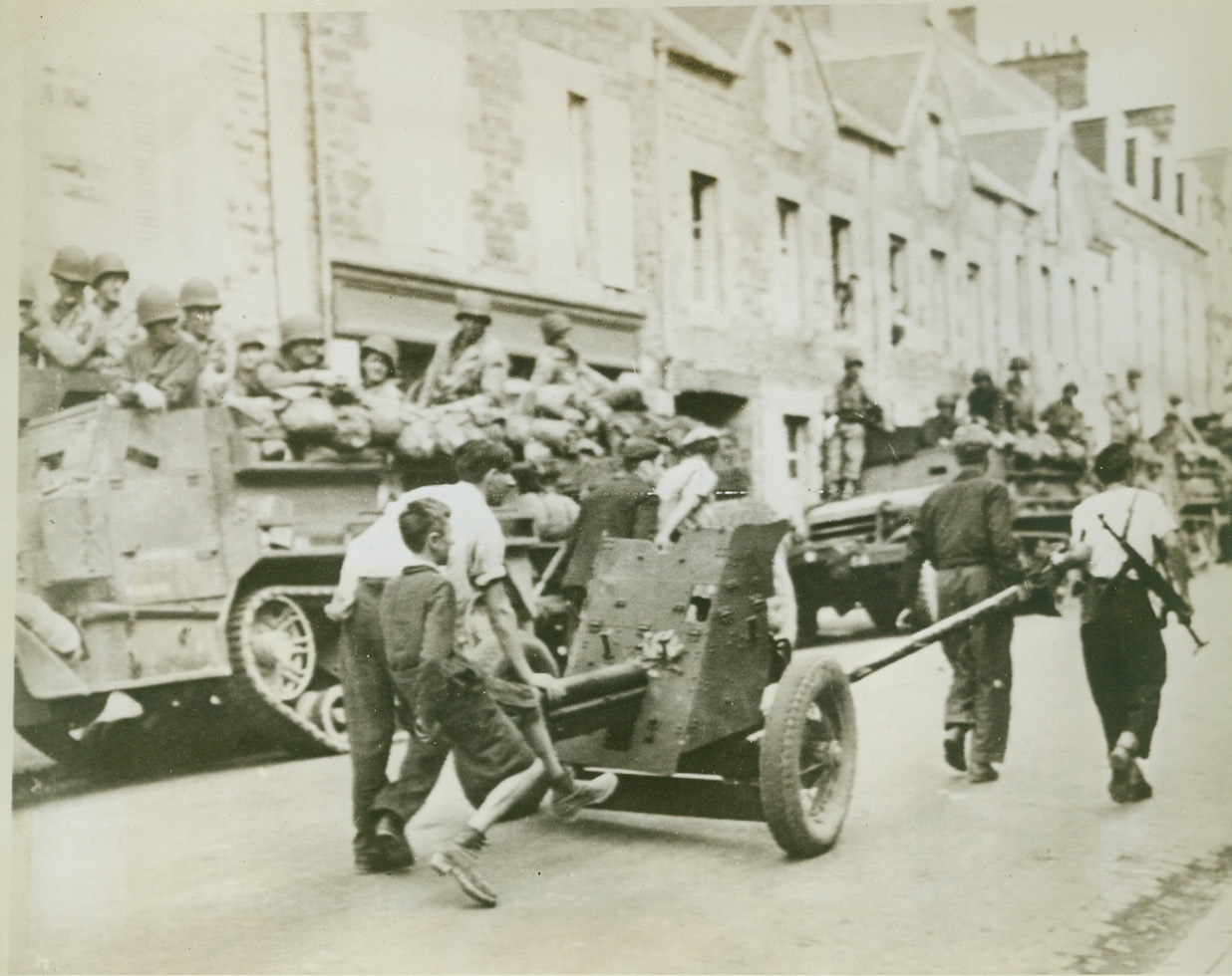 Frenchmen Retrieve German Gun, 8/4/1944. France—As American and Allied forces watch from trucks at the side of the road, civilians of Brehal, France, bring in German equipment left behind by the rapidly retreating Nazis. Little boy rides the barrel of a light infantry cannon being rolled through the town. Credit: Signal Corps radiotelephoto from ACME;