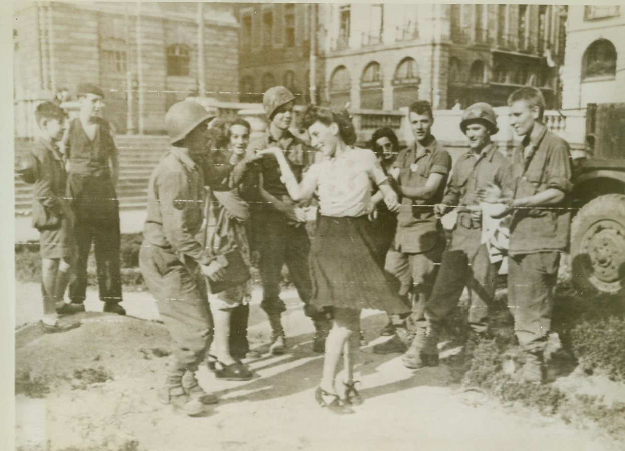 G. I. Jitterbugging, 8/6/1944. Rennes, France—So great was their joy over the Allied capture of Rennes that natives of that great city literally danced in the streets. Here a pretty French girl cuts a rug with Rosario Talliento, a G. I. from Brooklyn, New York. Credit: Signal Corps radiotelephoto from ACME;