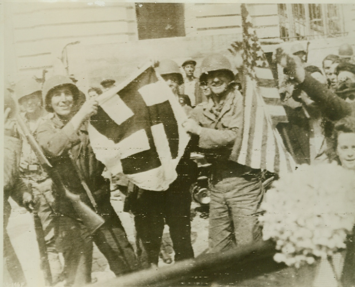 She'll Wave No More, 8/6/1944. Rennes, France—Smiling Yanks hold the flag that will fly no longer over liberated Rennes, capital of Brittany and largest French town to fall to the Allies to date. Beside the deposed Swastika, someone waves the Stars and Stripes, which, with the Tricolor, now waves over the city. Credit: Signal Corps radiotelephoto from ACME;