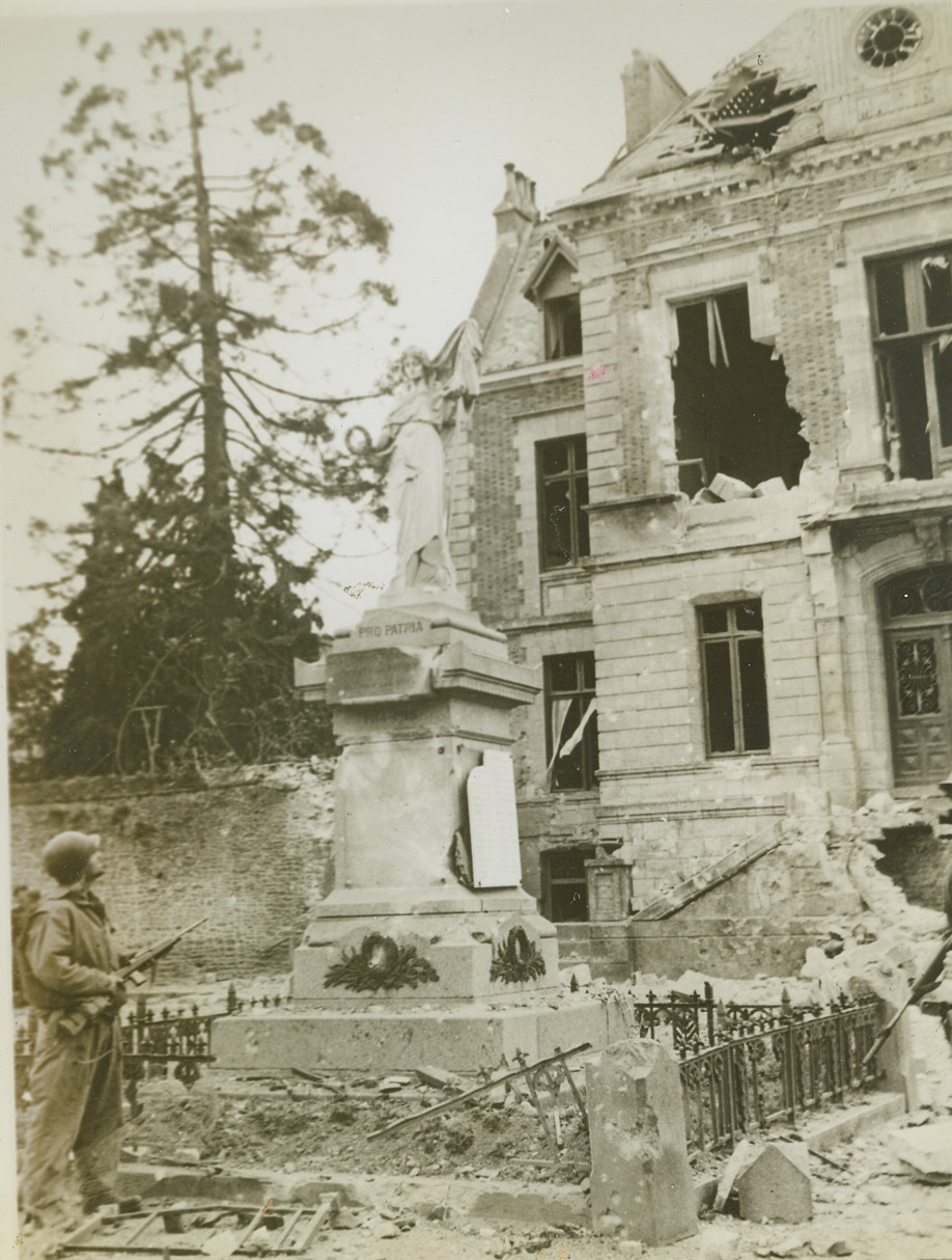 Before the ruins, 8/5/1944. France—Before the ruins of a war torn house in Periers, Normandy, Sgt. F. Clark, Marblehead, Mass., gazes at the statue of peace that somehow escaped damage. Only the pedestal has been chipped by shell fragments. With the rapid Nazi retreat on all fronts, this statue becomes a definite sign of the times.  Credit: ACME;